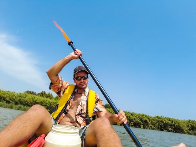 Een jonge man in de kano die kanoën in het natuurpark van catalonië, rivier naast het strand in estartit