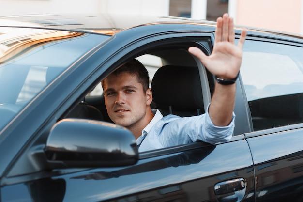 Een jonge man in een auto stak zijn hand uit het raam. de man keurt het goed