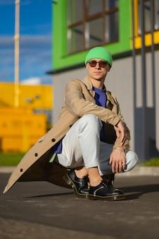 Een jonge man in een beige jas en groene hoed in de stad
