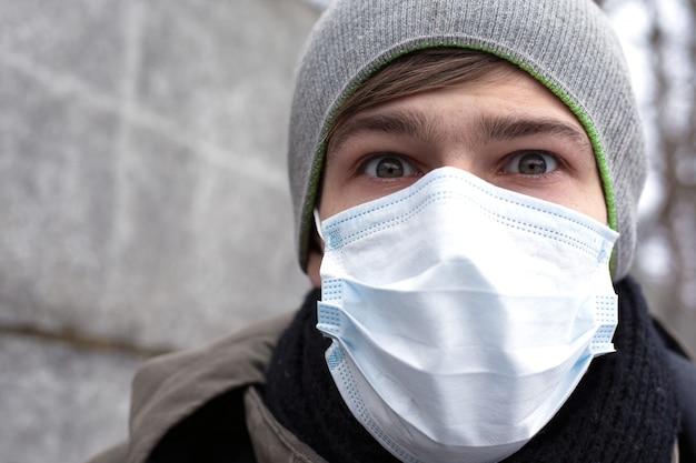 Een jonge man in een beschermend masker beschermt zichzelf tegen het coronavirus, een pandemie van het chinese virus. ncov-2019.