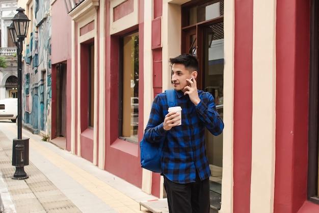 Een jonge man in een blauw geruit overhemd loopt over straat terwijl hij naar muziek luistert op zijn draadloze koptelefoon.