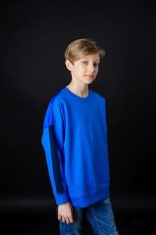 Een jonge man in een blauw t-shirt vormt op een zwarte achtergrond