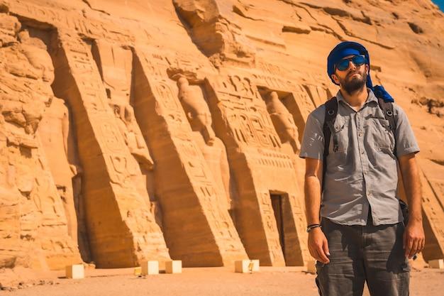 Een jonge man in een blauwe tulband en zonnebril bij de tempel van nefertari bij abu simbel in het zuiden van egypte in nubië naast het nassermeer. tempel van farao ramses ii, reislevensstijl