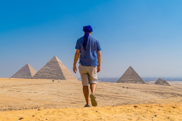 Een jonge man in een blauwe tulband loopt langs de piramides van gizeh, het oudste grafmonument ter wereld. in de stad caïro, egypte