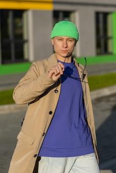 Een jonge man in een bruine jas en een groene hoed zette zijn bril af