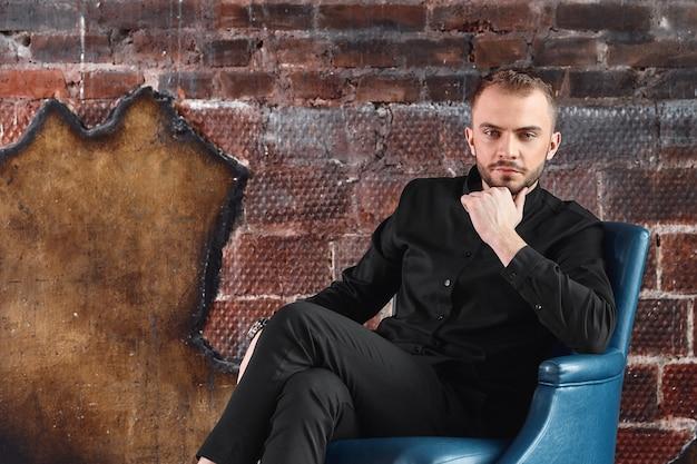 Een jonge man in een fauteuil in een zolderkamer kijkt naar de camera. geconfronteerd met moeilijkheden, niet bang voor moeilijkheden. verantwoordelijkheid nemen. kopieën van de ruimte.