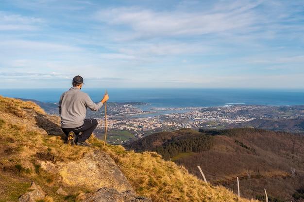Een jonge man in een grijze trui kijkt naar het uitzicht op de steden hondarribia en hendaya vanuit de bergen van aiako harria of peñas de aya, guipãºzcoa