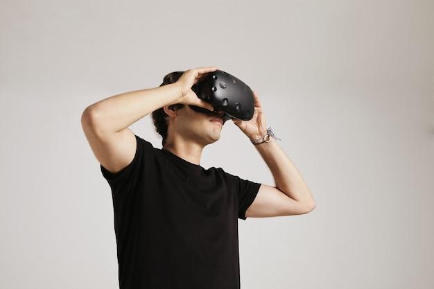 Een jonge man in een leeg zwart t-shirt zet een vr-bril op die op wit wordt geïsoleerd
