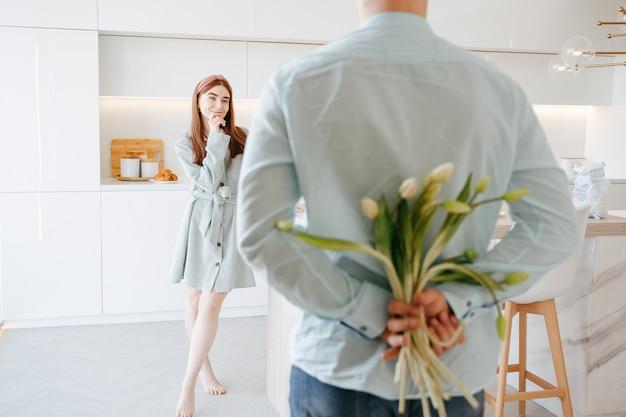 Een jonge man in een licht overhemd houdt thuis achter zijn rug een boeket tulpen als cadeau voor zijn vrouw. close-up van bloemen op 8 maart. gratis plaats.