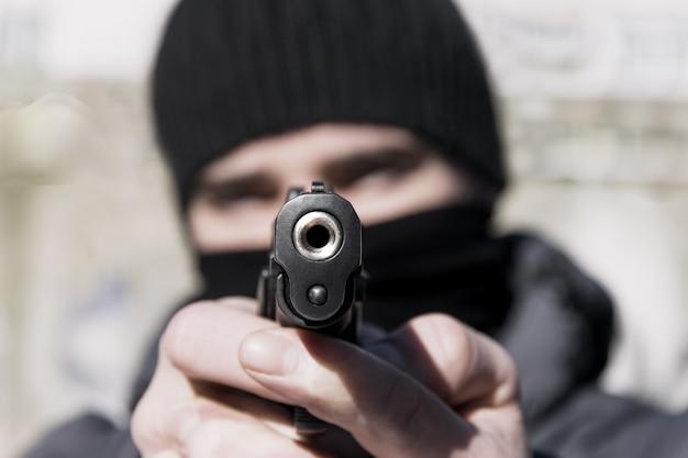 Een jonge man in een masker met een pistool in zijn handen. afgezwakt