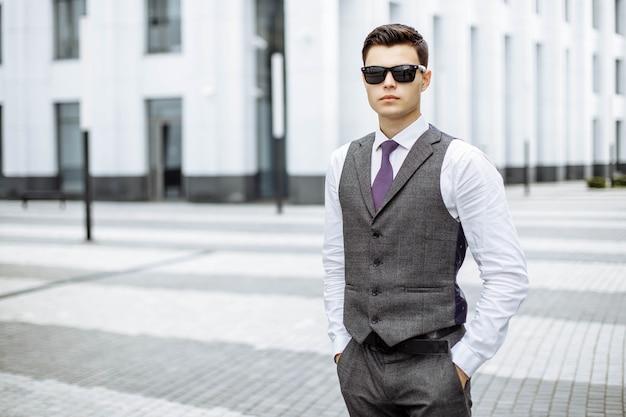 Een jonge man in een pak en een zonnebril buitenshuis in de stad