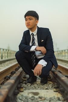 Een jonge man in een pak hurkte midden op een spoorbrug wegkijkend