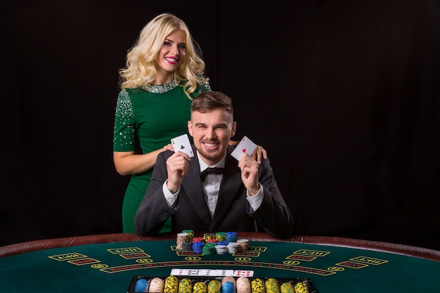 Een jonge man in een pak toont een paar azen. pokeren aan tafel. jonge vrouw geniet van winnen bij poker. ze kijken allebei naar de camera en glimlachen