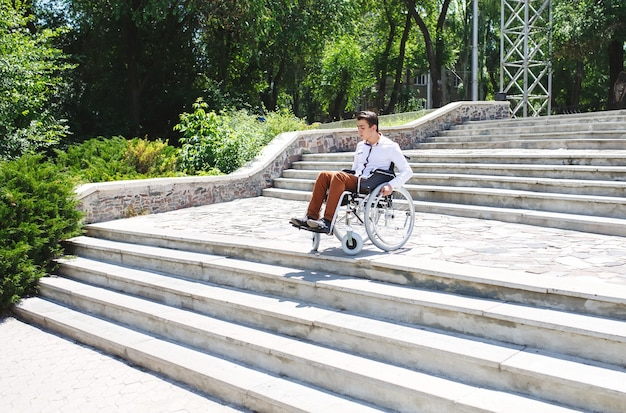 Een jonge man in een rolstoel die niet de trap af kan.