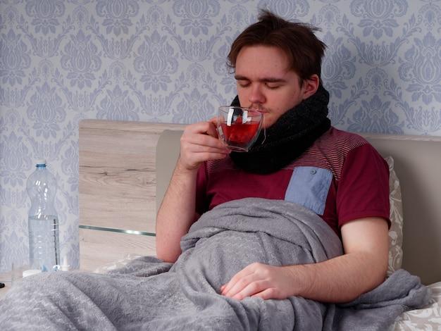 Een jonge man in een rood t-shirt zit op het bed en drinkt thee voor een verkoudheid, het concept van ziekte thuis