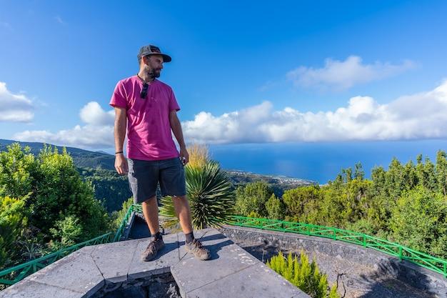 Een jonge man in een roze t-shirt bovenop de berg bij het uitzichtpunt van de cubo de la galga