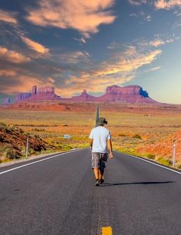 Een jonge man in een wit overhemd die bij zonsondergang op de weg naar monument valley loopt. utah