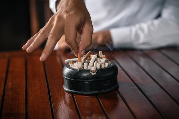 Een jonge man in een wit overhemd houdt een sigaret in zijn handen en slaat hem in een asbak vol sigaretten.