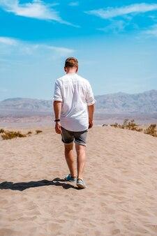 Een jonge man in een wit overhemd loopt door de pittoreske woestijn in death valley