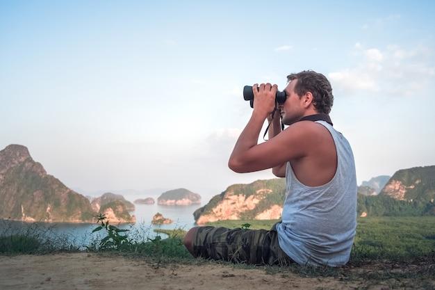 Een jonge man in een wit t-shirt zit bovenop en kijkt door een verrekijker in de verte naar een prachtig zeegezicht en rotsen.