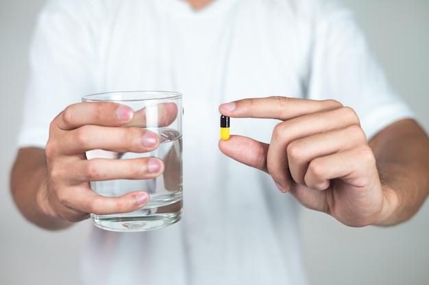 Een jonge man in een witte jurk staat op het punt een pil te eten.