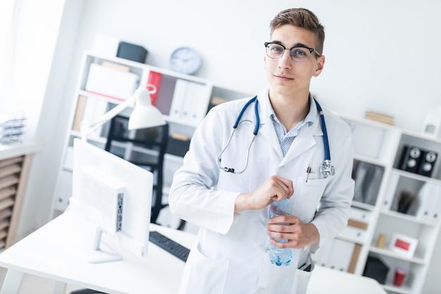 Een jonge man in een witte robe die zich in het kantoor bevindt en een fles water houdt.
