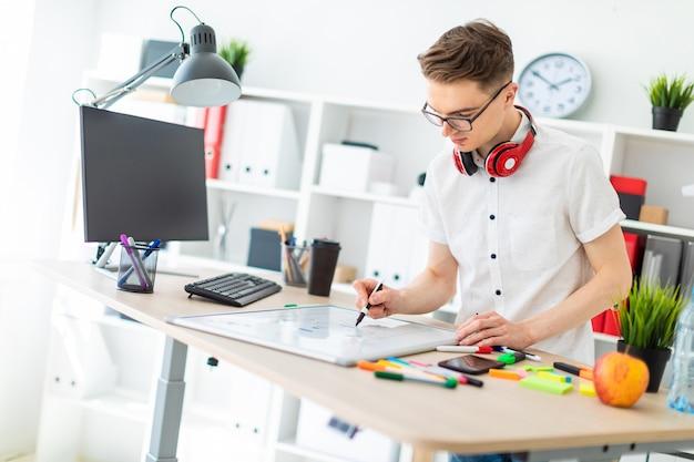 Een jonge man in glazen staat in de buurt van een computerbureau. een jonge man tekent een marker op een magnetisch bord. in de nek hangt de koptelefoon van de man.