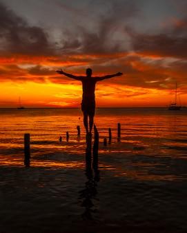 Een jonge man in het water bij de orange sunset op het strand van west end in roatan. honduras