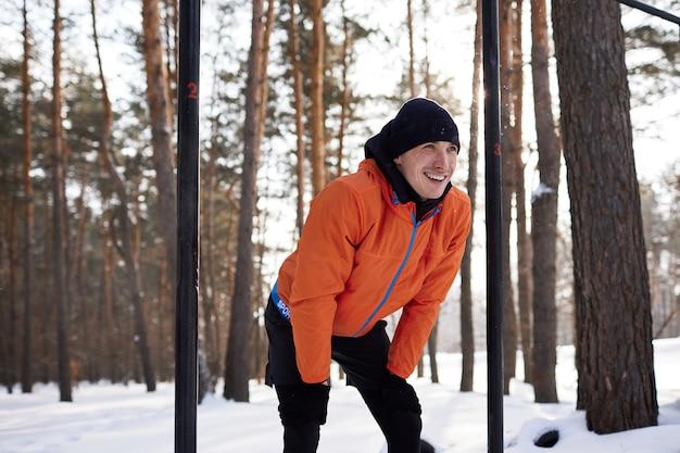 Een jonge man in lichte sportkleding houdt zich bezig met een training op een sportveld op een winterse dag