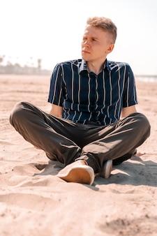 Een jonge man in overhemd rust op het zand van een strand in los angeles het concept van een zomervakantie summer