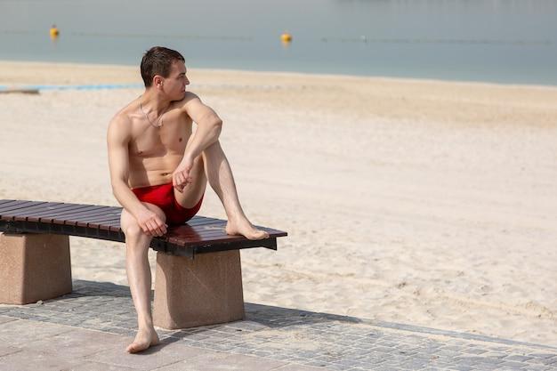 Een jonge man in rode zwembroek zonnebaadt liggend op een bankje aan het strand.