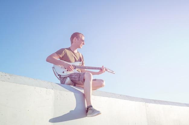 Een jonge man in zonnebril met een gitaar zit op de achtergrond van een wolkenloze hemel.