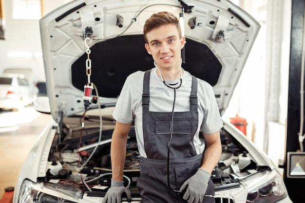 Een jonge man is aan het werk bij een autoservice.