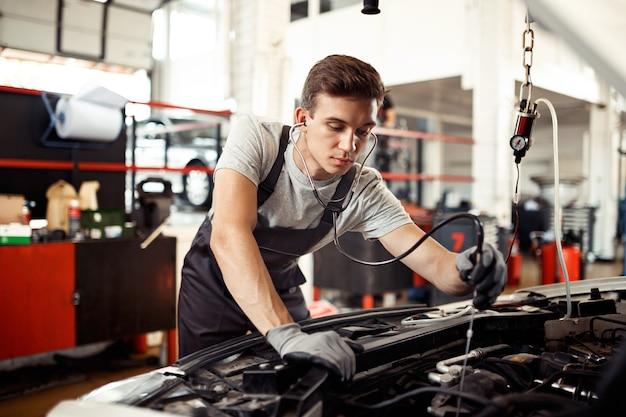 Een jonge man is bezig met het controleren van een automotor: autoreparatie en -onderhoud.