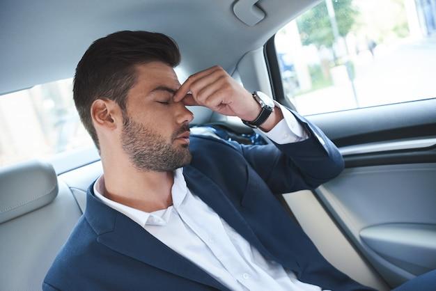 Een jonge man is van streek en zit in de grijze cabine van een luxe auto