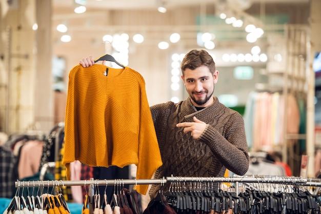 Een jonge man kiezen van kleding voor zijn vriendin in een winkel