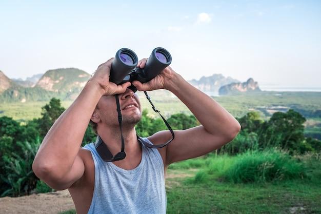 Een jonge man kijkt door een verrekijker naar de lucht. een reiziger op de achtergrond van de wilde natuur.