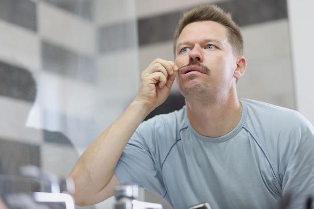 Een jonge man kijkt in de spiegel en trekt aan zijn snor. ontevredenheid over je uiterlijk. gezichtsverzorging voor mannen