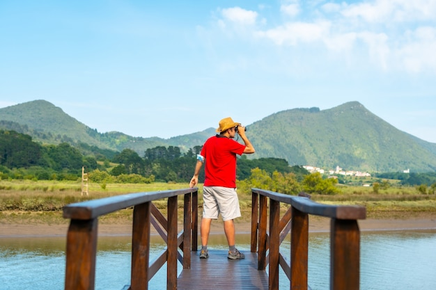 Een jonge man kijkt met een verrekijker naar vogels vanaf de houten pieren van de urdaibai-moerassen, een biosfeerreservaat in bizkaia naast mundaka. baskenland