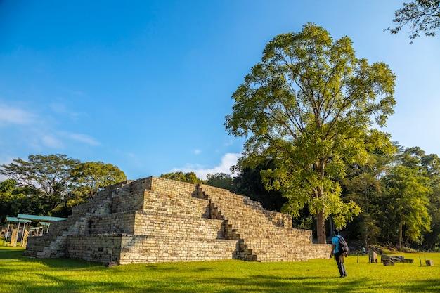Een jonge man kijkt naar een maya-piramide in de copan ruins-tempels