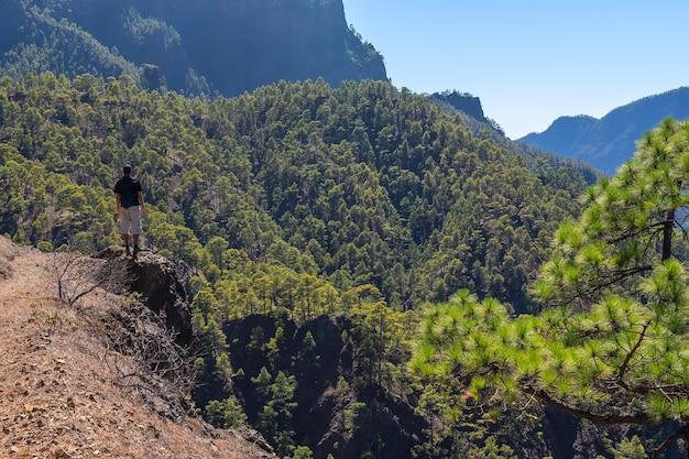 Een jonge man kijkt naar het landschap tijdens de trektocht vanaf de top van la cumbrecita naast de bergen van de caldera de taburiente, la palma eiland, canarische eilanden, spanje