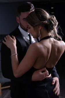 Een jonge man knoopt de avondjurk van zijn sexy vrouw los tijdens een knuffel