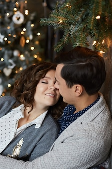 Een jonge man knuffelt zijn mooie vriendin terwijl hij thuis onder de kerstboom zit