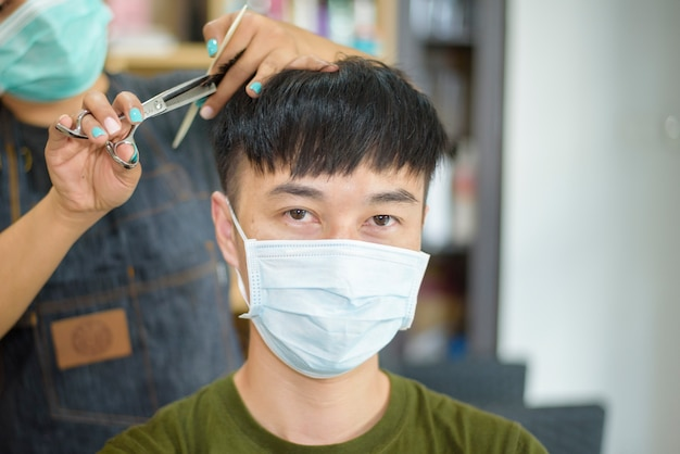 Een jonge man krijgt een knipbeurt in een kapsalon