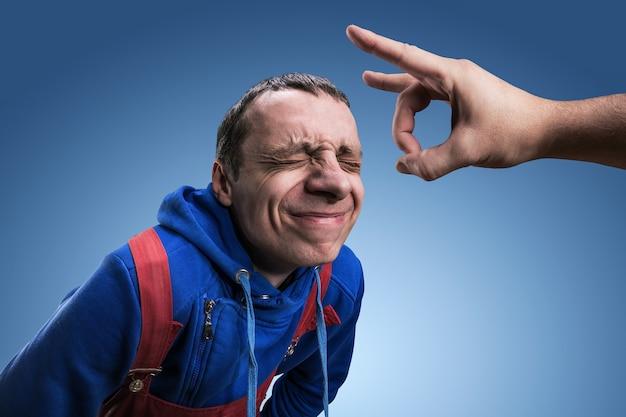 Een jonge man krijgt een lip op zijn voorhoofd tegen blauw Premium Foto
