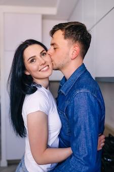 Een jonge man kust zijn vriendin, knuffelend terwijl hij in de keuken staat. het paar knuffelt.