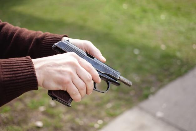 Een jonge man laadt een pistool tegen een groen gras. vuurwapens pistool