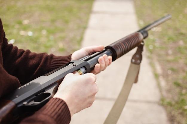 Een jonge man laadt een shotgun met pompactie op met een munitie.