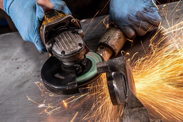 Een jonge man lasser in een blauwe handschoenen grinder metaal een haakse slijper in de werkplaats, vonken vliegen naar de zijkant