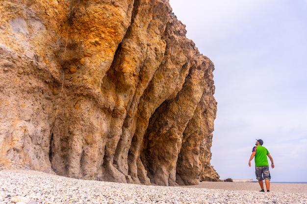 Een jonge man loopt en kijkt naar de prachtige natuurlijke muren van playa de los muertos in het natuurpark van cabo de gata, nijar, andalusië. spanje